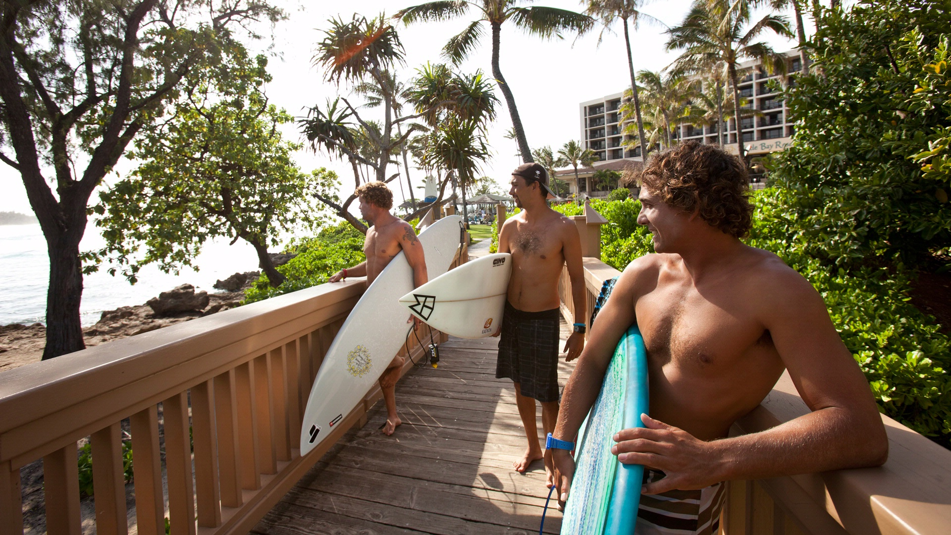 Group of 3 friends with surfboard looking out over water