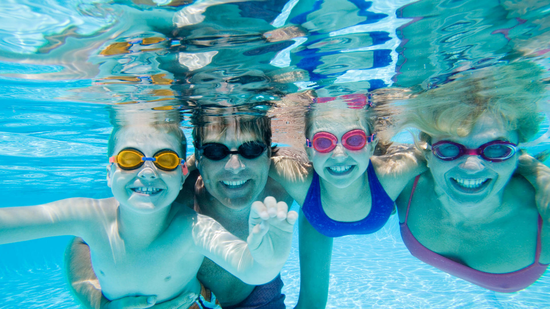 family underwater in a pool with goggles on