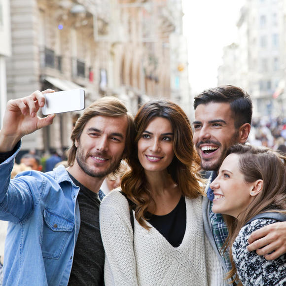 4 people smiling and taking a selfie