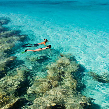 Couple snorkeling in crystal blue water