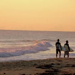 2 friends on the beach preparing to surf