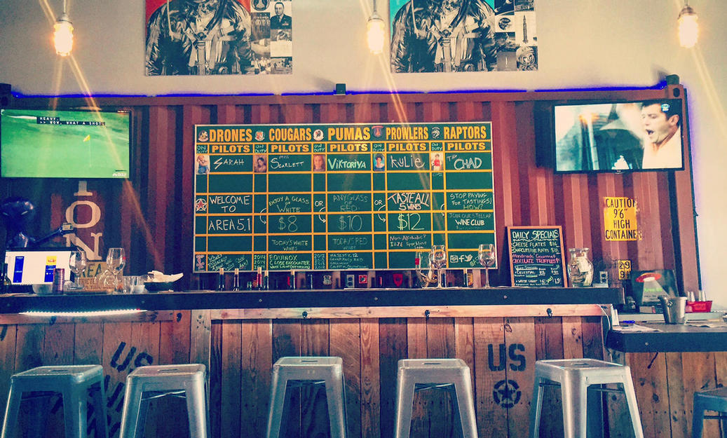 Bar seating area with scoreboard in background