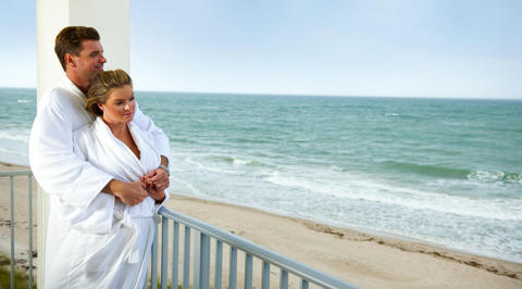 Couple in bathrobes looking out over beach