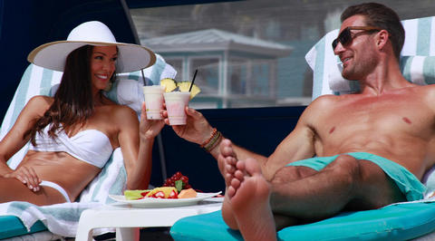 Couple drinking piña coladas on sun loungers
