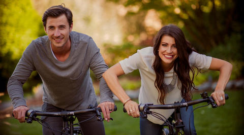 2 people smiling riding bikes
