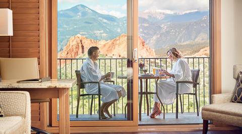 Couple eating breakfast on balcony with mountains in distance