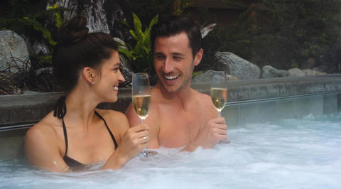 2 people drinking champagne in hot tub