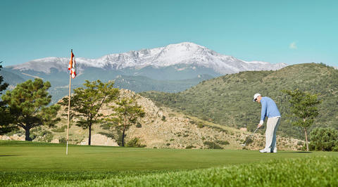 Man putting on the green with mountains in background