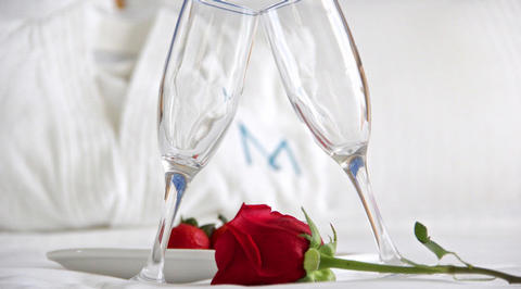 2 champagne glasses touch with red rose in the middle