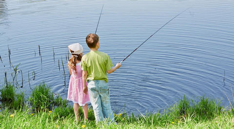 2 children fishing in lake