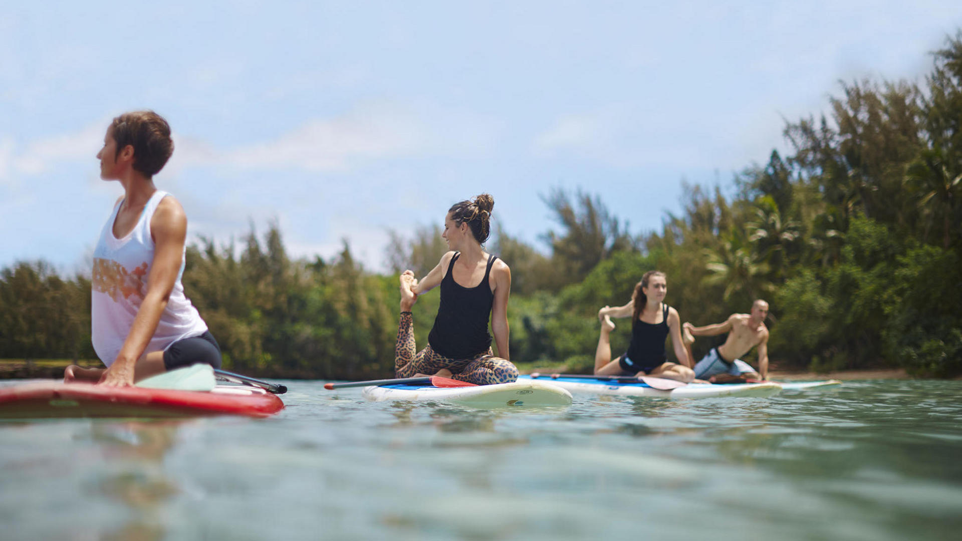 people doing yoga on paddle boards