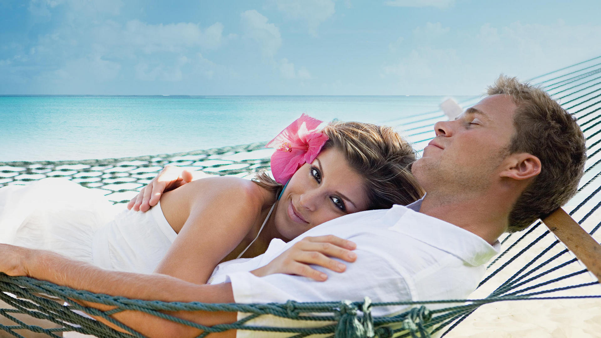 Couple lying together on a hammock on beach