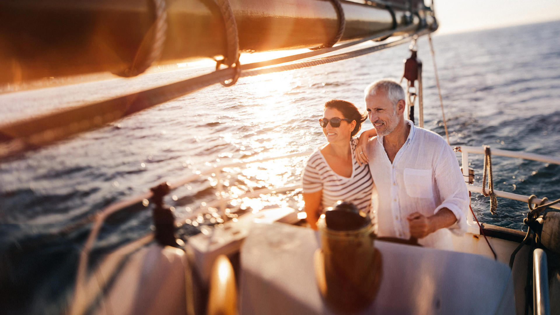 Elderly couple smiling while sailing on a boat