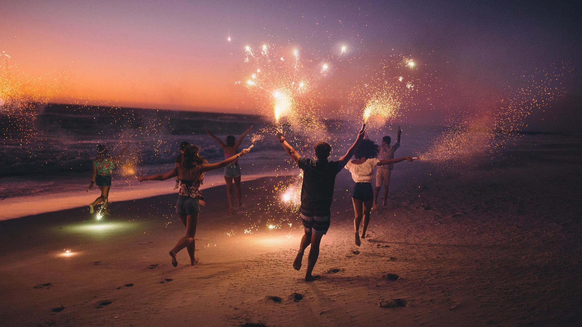 group of people running on the beach with sparklers